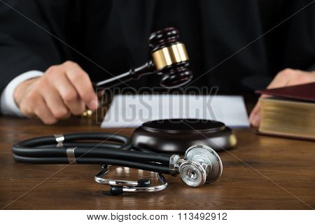 Judge Striking Mallet With Stethoscope At Desk