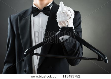 Midsection Of Male Housekeeper Holding Hanger
