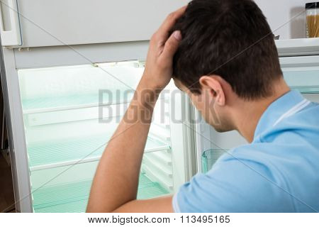 Confused Man Scratching Head While Looking At Empty Refrigerator