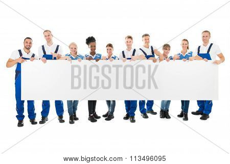 Happy Multiethnic Cleaners Holding Blank Billboard
