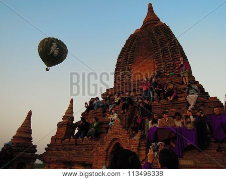 People are sitting on a temple to watch the sunrise