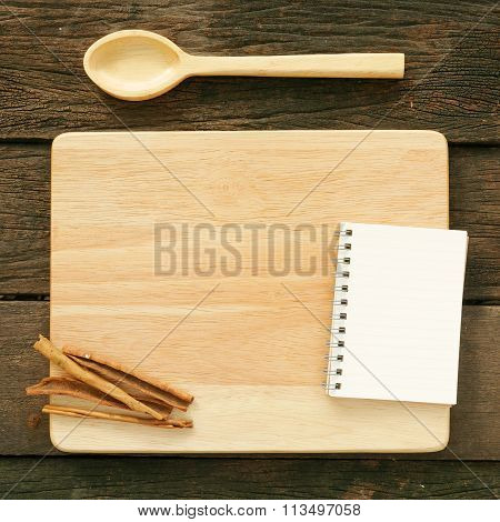 Wooden board and spoon and blank earth tone note book with cinnamon
