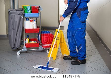 Janitor With Broom Cleaning Office Corridor