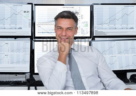 Confident Stock Market Broker Leaning On Desk