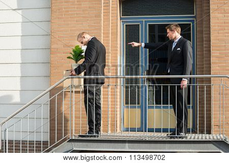 Businessman Firing Employee Outside Office