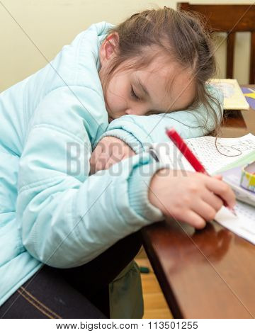 Young Girl Falling Asleep Doing Homework
