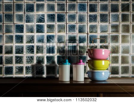 Colorful Tiffin Carrier And Plastic Bottles On Wooden Cupboard With Vintage Tiles Wall Background