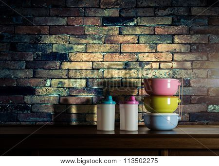 Colorful Tiffin Carrier And Plastic Bottles On Wooden Cupboard With Vintage Brick Wall Background