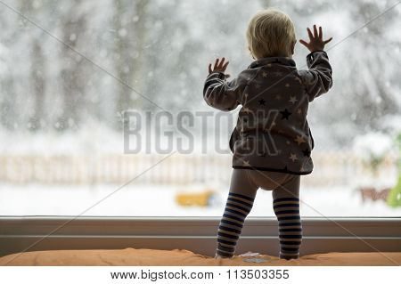 Toddler Child Standing In Front Of A Big Window Leaning Against It Looking Outside