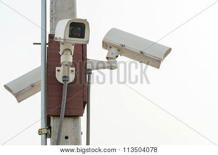 Three Surveillance Security Cameras On White Sky Background