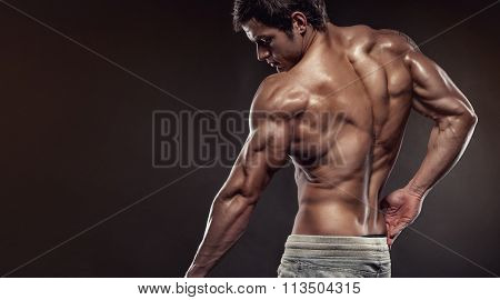 Strong Athletic Man Fitness Model Posing Back Muscles With Triceps, Copyspace