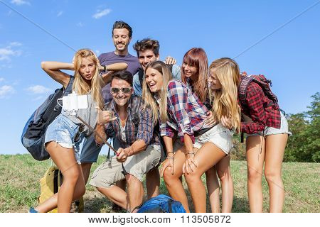 group of friends taking a self portrait with selfie stick