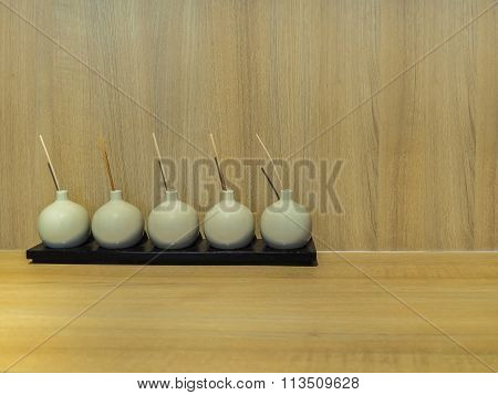 Rounded Bottles Contain Deodorant Perfume On Black Wooden Plate