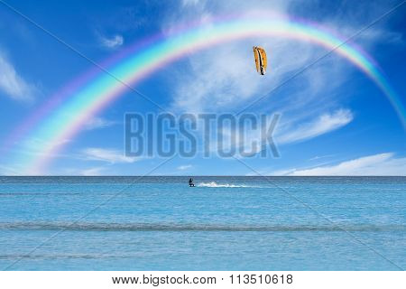 Kitesurfer In Action On Clear Blue Water Under A Rainbow