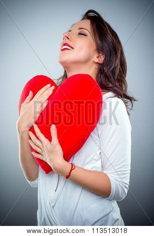 Young Woman In Love Clutching A Red Heart
