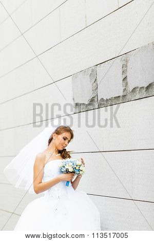 Portrait of  young bride in  white dress with a wedding bouquet