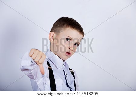 Upset little boychild thumb down isolated over yellow background.Facial expression