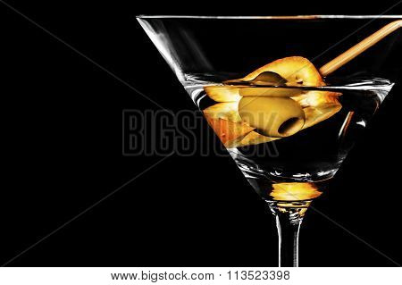 Close-up of dry martini with green olives and an orange slice on a black background