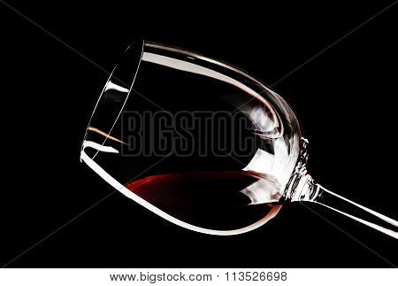 Close-up of a glass of red wine on a black background in the horizontal format