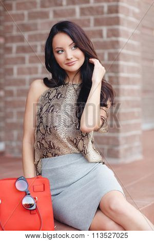 Beautiful young woman, model of fashion, in urban background