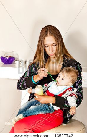 Young beautiful mother is feeding her cute  little boy with a puree in modern surrounding.