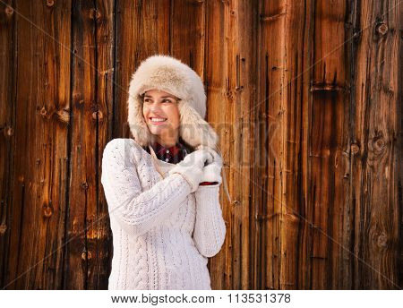 Happy Woman In White Sweater And Furry Hat Near Rustic Wood Wall