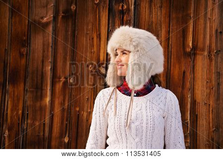 Happy Woman In Furry Hat Near Rustic Wood Wall Looking Aside