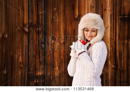 Relaxed And Dreamy Woman With Red Cup Near Rustic Wood Wall