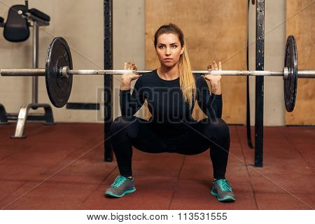 Young strong girl in the gym doing squat