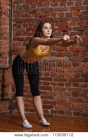 Sport Brunette Doing Exercise On A Brick Wall Background