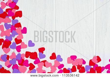 Valentines Day paper heart corner border against white wood