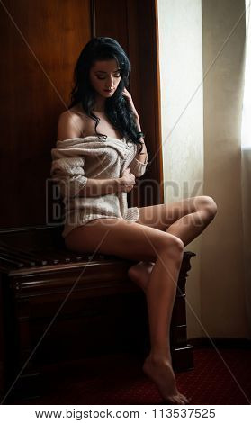 Attractive sexy brunette half naked posing provocatively in window frame. Portrait of sensual woman