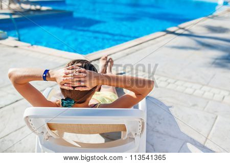Woman Chaise Longue On The Background Of The Pool At The Hotel