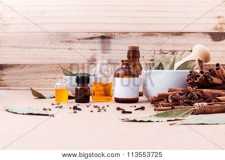 Bottle Of Essential Oil With Cinnamon Stick ,star Anise ,bay Leaves With Selective Focus On Old Wood