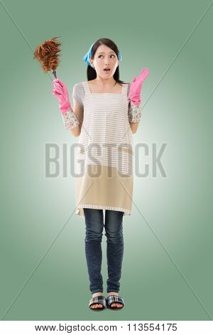 Portrait of Asian housewife using feather duster, full length portrait
