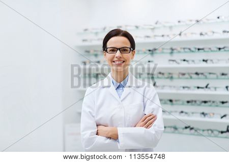 woman optician in glasses and coat at optics store