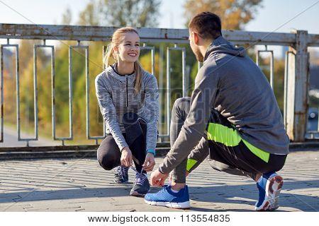 smiling couple tying shoelaces outdoors