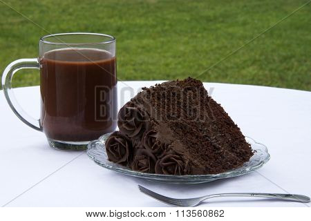 slice of triple chocolate cake on a plate with chocolate milk