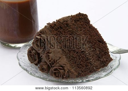 Slice of Triple Chocolate Rose Cake on glass plate with chocolate milk close up