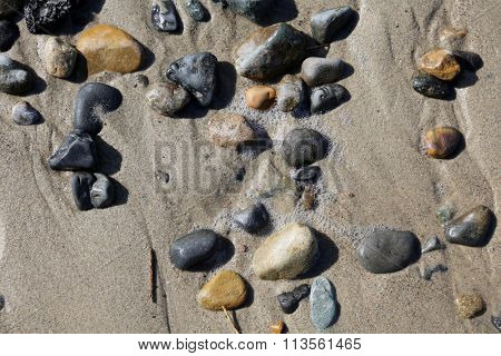 Round stones and rocks smoothed by the ocean, waves and tides lay piled in the sand on the beach. Rocks of various types of minerals can be found on the beach.