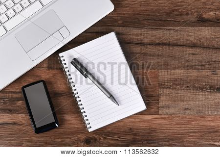 A laptop computer, pen, paper pad and cell phone on a dark wood desk. Horizontal format with copy space.