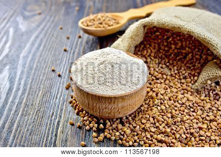 Flour buckwheat in bowl and spoon with cereals on board