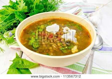 Soup lentil with spinach and feta in yellow bowl on board