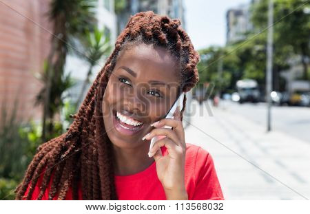 African Woman With Dreadlocks Laughing At Phone In The City