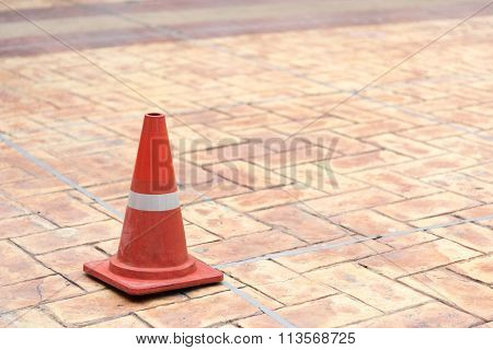 Red Traffic Cone On Tiled Rock Pavement