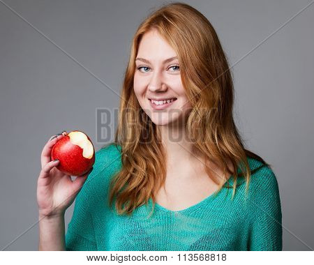 Portrait Of A Young Ginger Woman In Green Blouse With Bitten Apple