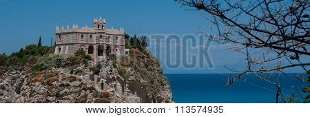 Church on top of rock hill at the sand beach coast in Tropea