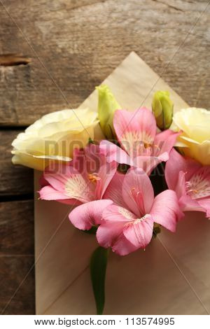White eustoma and pink alstroemeria in envelope on wooden background