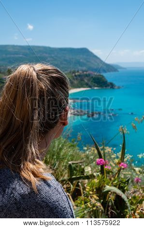 Blond woman from behind looking over beautiful coast of calabria fronting the blue mediterranean sea