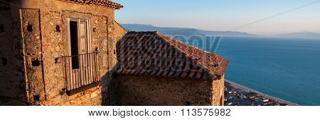 Old Italian stone house over small town by the sea